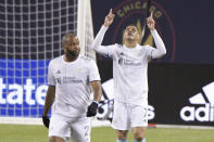 New England Revolution forward Gustavo Bou (7), right, celebrates his goal against the Chicago Fire during the first half of an MLS soccer match in Chicago, Saturday, April 17, 2021. (AP Photo/Mark Black)