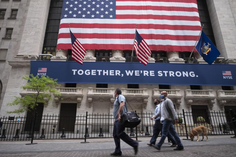 People wearing protective face masks pass the New York Stock Exchange, Tuesday, May 26, 2020, as employees arrive for the partial reopening of the trading floor. (AP Photo/Mark Lennihan)