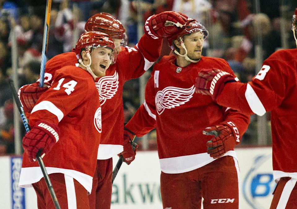 From left to right, Detroit Red Wings forward Gustav Nyquist (14), forward Johan Franzen and defenseman Niklas Kronwall, all of Sweden, celebrate a goal during the first period of an NHL hockey game against the Tampa Bay Lightning in Detroit, Mich., Sunday, Nov. 9, 2014. (AP Photo/Tony Ding)