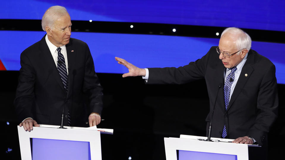 Former Vice President Joe Biden, left, watches as Sen. Bernie Sanders, I-Vt., answers a question during Tuesday's Democratic presidential primary debate in Des Moines. (AP Photo/Patrick Semansky)