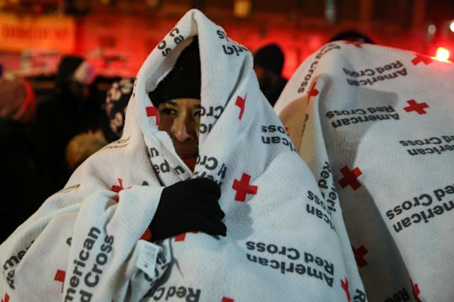 <p>Evacuees wear blankets as they stand after a fire at an apartment building in Bronx, New York, Dec. 28, 2017. (Photo: Amr Alfiky/Reuters) </p>