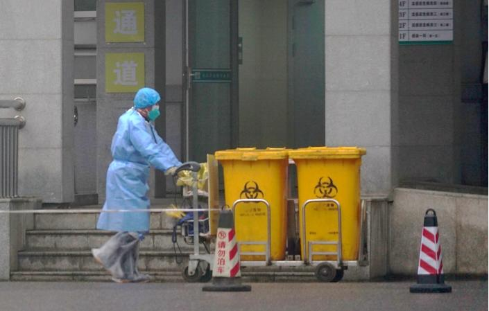 "A worker moves bio-waste containers past the entrance of the Wuhan Medical Treatment Center in Wuhan, China, on Jan. 22, 2020. <span class=""copyright"">(Associated Press )</span>"
