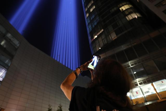 <p>A woman takes a photo of the Tribute in Light with her mobile device on Sept. 11, 2017. (Gordon Donovan/Yahoo News) </p>