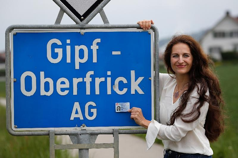 Nancy Holten poses with her Swiss identity card next to a road sign in her home village -- but direct democracy, Swiss-style, ensured getting the document was a complex process (AFP Photo/STEFAN WERMUTH)