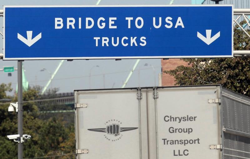 A commercial automotive supplier truck passes under a sign leading to the Ambassador bridge crossing over to Detroit, Michigan from Windsor, Ontario