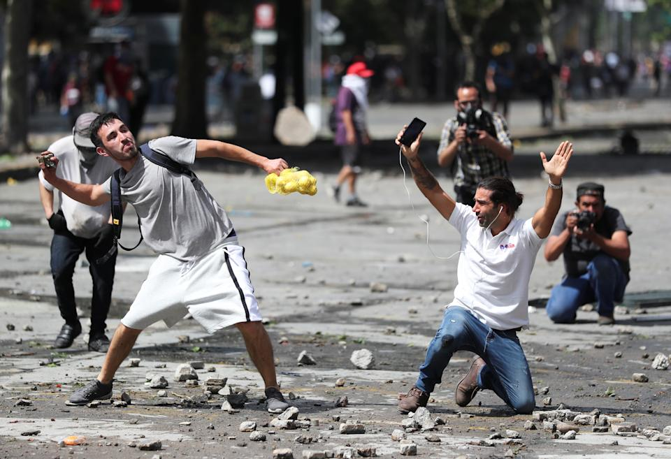 A demonstrator throws a rock during a protest against Chile's state economic model in Santiago, Chile on Oct. 23, 2019. (Photo: Ivan Alvarado/Reuters)