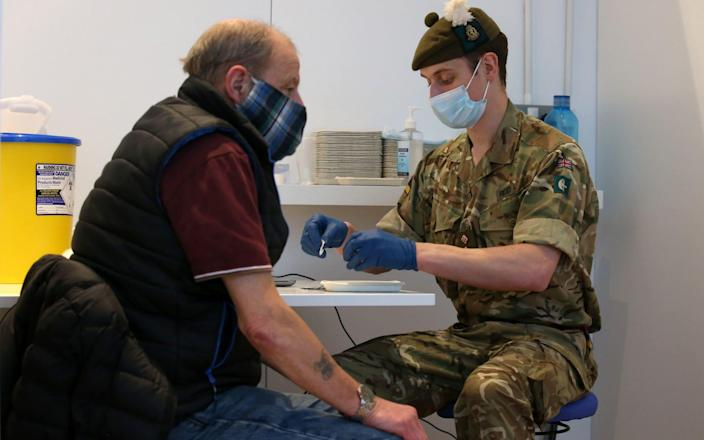 Derek Fraser from Edinburgh receives an injection of a coronavirus vaccine from military doctor Captain Robert Reid from 3 Medical Regiment who are assisting with the vaccination programme at the Royal Highland Showground near Edinburgh - PA