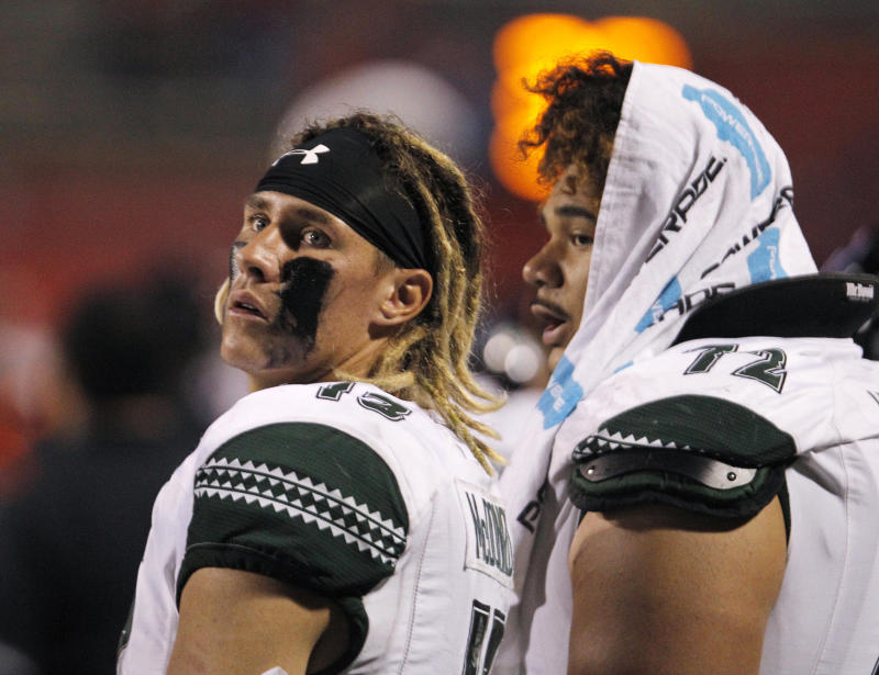 Hawaii quarterback Cole McDonald, left, checks the scoreboard in a blowout loss to Fresno State during the second half of an NCAA college football game in Fresno, Calif., Saturday, Oct. 27, 2018. Fresno State won 50-20. (AP Photo/Gary Kazanjian)