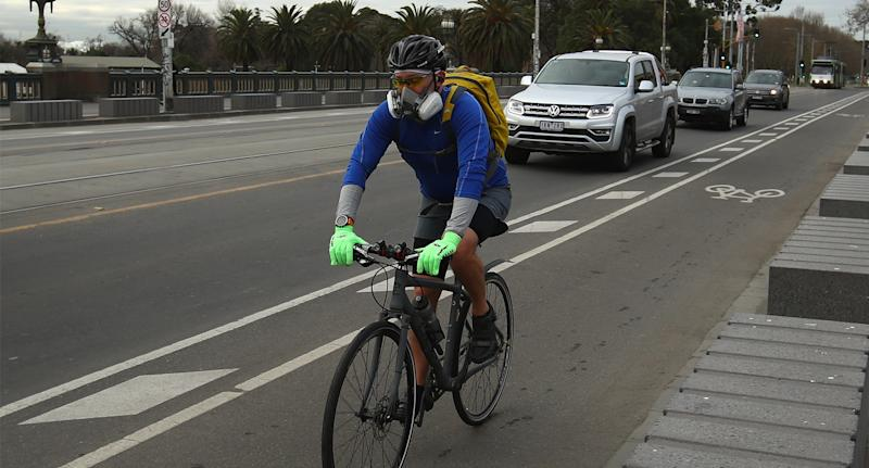 Photo shows a cyclist on a Melbourne road wearing a face mask.
