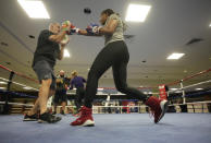 USA Boxing team member Naomi Graham, right, spars with head coach Billy Walsh during a media day for the team in a gym located in a converted Macy's Department store in Colorado Springs, Colo., Monday, June 7, 2021. Naomi Graham feels no extra pressure in taking up Claressa Shields' mantle at 75 kilograms in Tokyo. Six years older than Shields, she's a relative newcomer to high-level boxing, only picking it up a decade ago and fighting her way to Olympic contention while also serving in the Army as an ammunition specialist. (AP Photo/David Zalubowski)