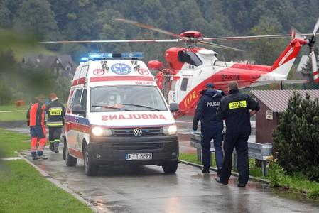 TOPR (Tatra Volunteer Search and Rescue) helicopter and an ambulance are seen as rescuers conduct a rescue operation after a thunderstorm in the Tatra Mountains, in Zakopane