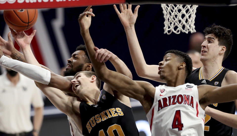 Arizona forward Jordan Brown (21), left, and guard Dalen Terry (4) tangle with Washington guard Erik Stevenson (10) and center Riley Sorn (52) for control of a rebound in the first half of an NCAA college basketball game Saturday, Feb. 27, 2021, in Tucson, Ariz. (Kelly Presnell/Arizona Daily Star via AP)