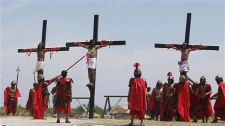 Penitents hang on wooden crosses during the re-enactment of the crucifixion of Jesus Christ on Good Friday in San Fernando, Pampanga