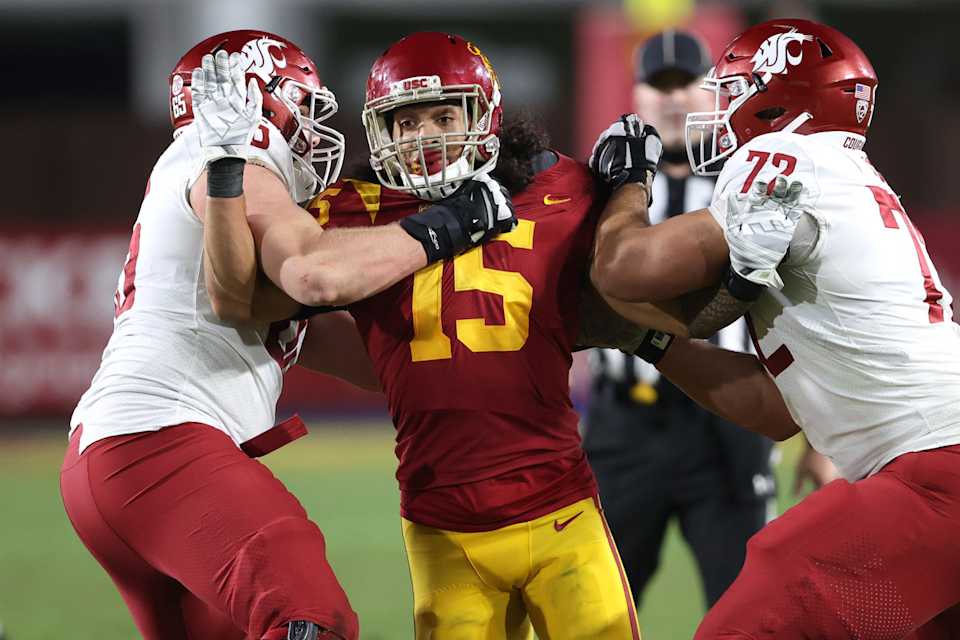 Washington State offensive linemen Abraham Lucas, right, and Josh Watson try to block USC's Talanoa Hufanga.