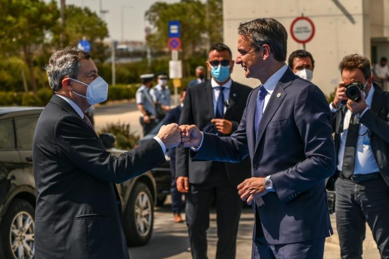 Greek Prime Minister Kyriakos Mitsotakis and Italy's Prime Minister Mario Draghi, masked, share a fist-bump greeting ahead of the outhern European summit in Athens (AFP/Angelos Tzortzinis)
