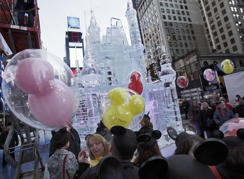 "People with mouse ear caps and balloons gather near a three-story castle mad of ice in New York's Times Square,  Wednesday, Oct. 17, 2012. On Wednesday, Disney announced a new program for 2013, ""Limited Time Magic,"" in which guests will encounter surprise weekly themes at Disney parks in Florida and California.  The program was described as ""52 weeks of magical experiences big and small that appear, then disappear as the next special surprise debuts."" For example, a weeklong Valentine's Day celebration might include pink lighting on Disney castles, surprise meet-and-greets with Disney characters and candlelit dinners for lovebirds. (AP Photo/Richard Drew)"