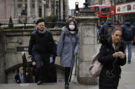 A woman wearing a face mask exits Bank underground train station in London, Wednesday, March 4, 2020. British authorities laid out plans Tuesday to confront a COVID-19 epidemic, saying that the new coronavirus could spread within weeks from a few dozen confirmed cases to millions of infections, with thousands of people in the U.K. at risk of death. (AP Photo/Matt Dunham)