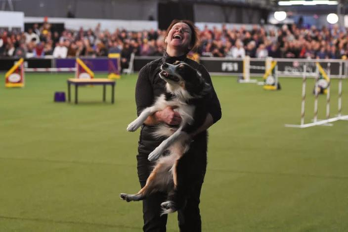 A woman celebrates with her dog after participating in the Masters Agility Championship during the Westminster Kennel Club Dog Show in New York