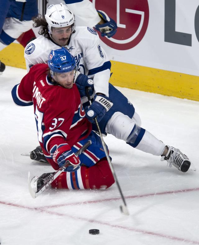 Montreal Canadiens' Gabriel Dumont and Tampa Bay Lightning Mark Barberio fall to the ice as they reach for the puck during the second period of an NHL hockey game Tuesday, Nov. 12, 2013, in Montreal. (AP Photo/The Canadian Press, Paul Chiasson)