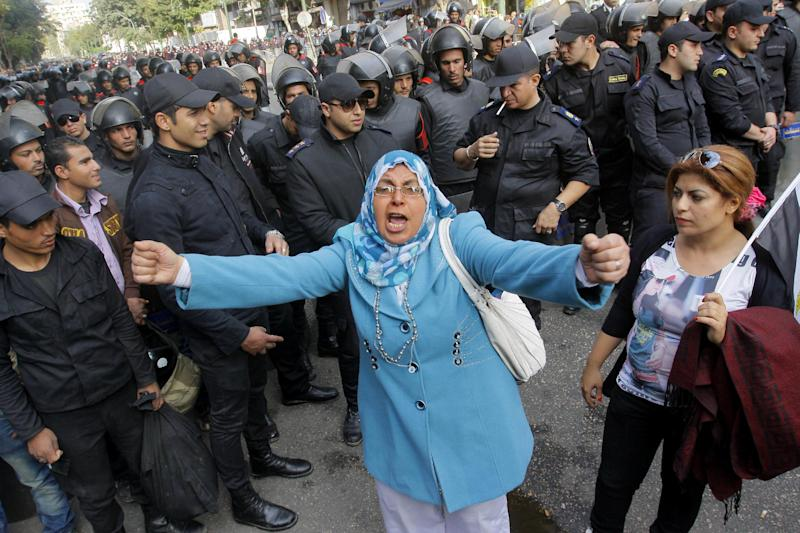 An Egyptian woman shouts anti-Mohammed Morsi slogans as soldiers block a road leading to the Shura Council where the president addressed the upper house of parliament in Cairo, Egypt, Saturday, Dec. 29, 2012. Egypt's Islamist president warned Saturday against any unrest that could harm the drive to repair the country's battered economy in a sharply worded speech that urged the opposition to work with his government. Mohammed Morsi made the comments in his first speech to the newly convened upper house of parliament, which he said will have full legislative powers until a new lower house of parliament is elected next year. (AP Photo/Amr Nabil)