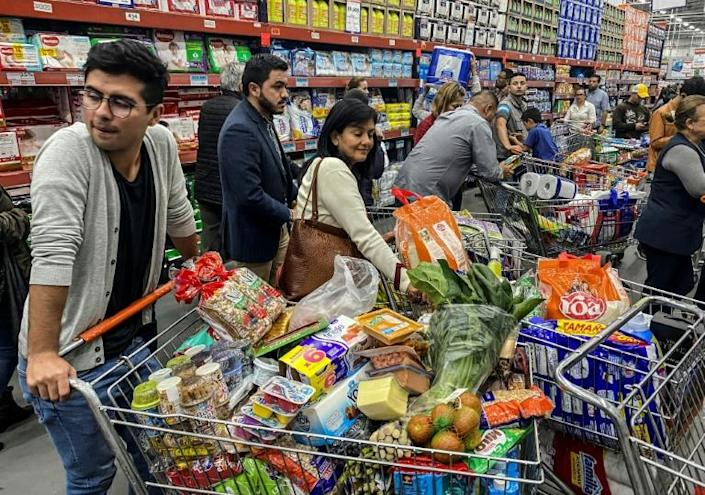 People rush to buy food and supplies in a supermarket before quarantine hits in Bogota, Colombia (AFP Photo/Daniel MUNOZ)