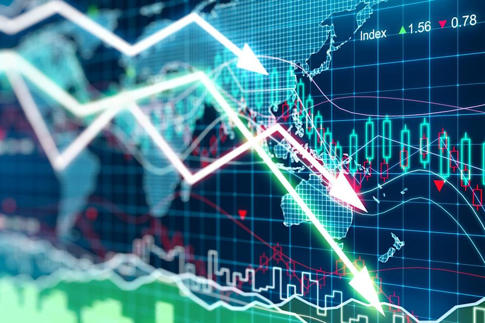 Falling stock charts superimposed over digital map of the world