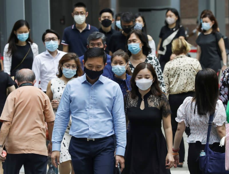 Office workers wearing masks cross a street during lunch hour, amid the coronavirus disease (COVID-19) outbreak, in Singapore