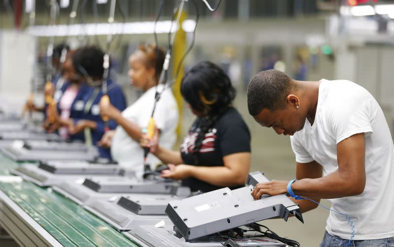 Workers on the assembly line replace the back covers of 32-inch TV sets at Element Electronics in Winnsboro