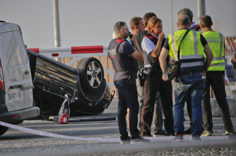 Police officers speak near an overturned car at the spot where terrorists were intercepted by police in Cambrils. (AP Photo/Emilio Morenatti)