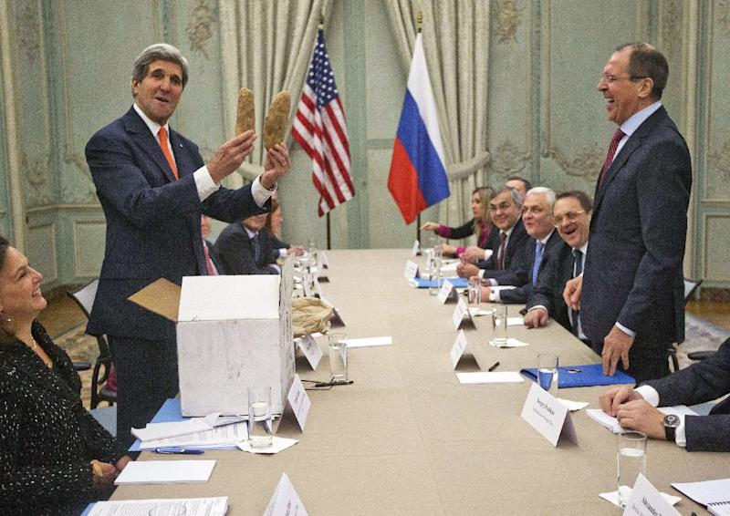 U.S. Secretary of State John Kerry holds up a pair of Idaho potatoes as a gift for Russia's Foreign Minister Sergey Lavrov, standing right, at the start of their meeting at the U.S. Ambassador's residence in Paris, France, Monday, Jan. 13, 2014. Kerry is in Paris on a two-day meeting on Syria to rally international support for ending the three-year civil war in Syria. For some watchers of international diplomacy, the somber road to Syrian peace was overrun Monday by potatoes and furry pink hats. (AP Photo/Pablo Martinez Monsivais, Pool)