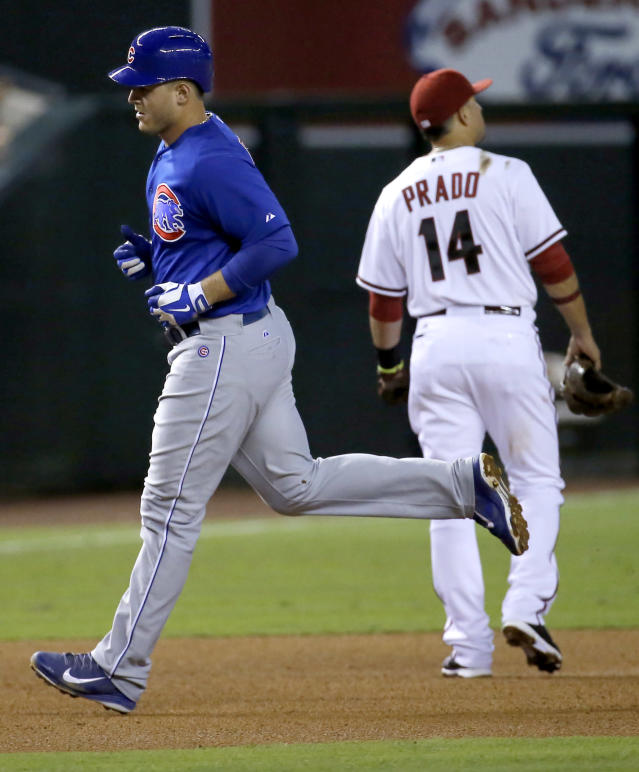 Chicago Cubs' Anthony Rizzo rounds the bases after hitting a two run home run as Arizona Diamondbacks' Martin Prado walks away during the fourth inning of a baseball game, Friday, July 18, 2014, in Phoenix. (AP Photo/Matt York)