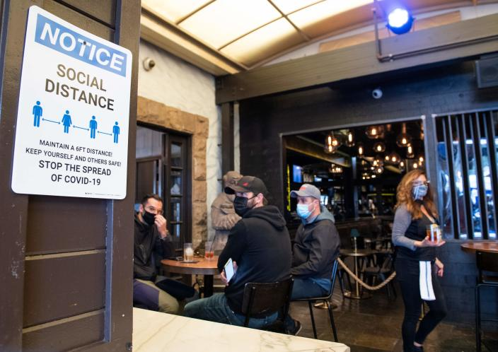 A notice inviting patrons to social distance is seen in the outdoor seating area of The Abbey Food & Bar on January 29, 2021 in West Hollywood, California. (Valerie Macon/AFP via Getty Images)