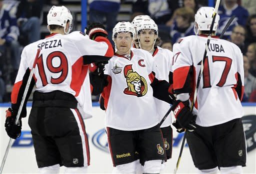 Ottawa Senators right wing Daniel Alfredsson, center, of Sweden, celebrates his goal against the Tampa Bay Lightning with Jason Spezza (19) and Filip Kuba (17) during the second period of an NHL hockey game, Tuesday, Feb. 14, 2012, in Tampa, Fla. (AP Photo/Chris O'Meara)