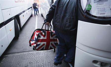 A man carrying a bag adorned with a British Union Jack flag steps into bus departing from Sofia's central bus station to London