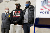 Terrence Floyd, brother of George Floyd, second from left, waits to vote with Sandy Rubenstein, left, and Rev. Kevin McCall, Tuesday, Nov. 3, 2020, in the Brooklyn borough of New York. (AP Photo/Frank Franklin II)
