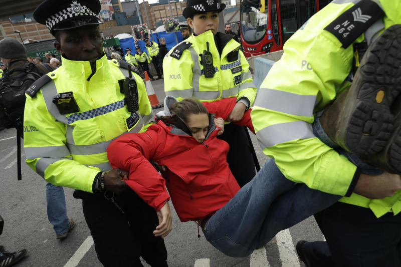 An Extinction Rebellion climate change protester is removed by police from blocking a road outside City Airport in London, Thursday, Oct. 10, 2019. Some hundreds of climate change activists are in London during a fourth day of world protests by the Extinction Rebellion movement to demand more urgent actions to counter global warming. (AP Photo/Matt Dunham)