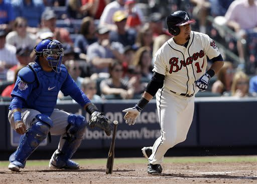 Atlanta Braves shortstop Ramiro Pena (14) follows through with a two-run base hit as Chicago Cubs catcher Dioner Navarro, left, looks on in the sixth inning of a baseball game in Atlanta, Sunday, April 7, 2013. (AP Photo/John Bazemore)