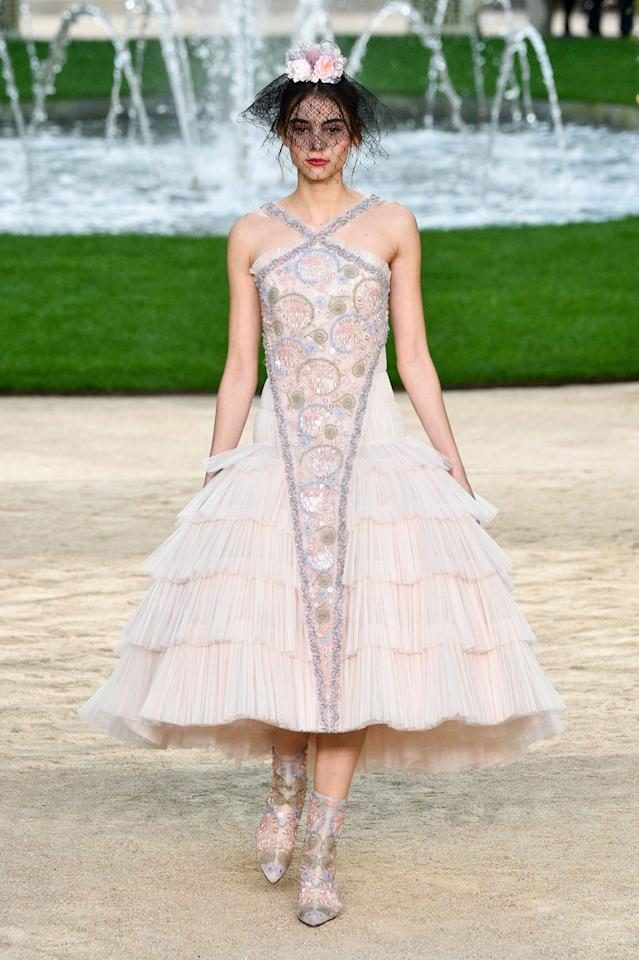 <p>Model wears a blush pink pleated halter dress with colored crystal embellishments from the Chanel SS18 Haute Couture show. (Photo: Getty Images) </p>