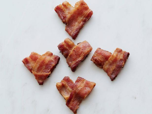 <p>Start your Valentine's Day off the right way with your sweetie's other true love: bacon. Fold strips into hearts on a baking sheet (inset with a rack if you have one) and bake at 400 degrees F until crisp.</p>