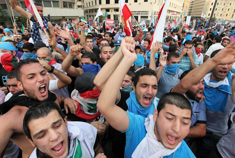 Lebanese protesters chant slogans against the Lebanese government after the funeral of Brig. Gen. Wissam al-Hassan, who was assassinated on Friday by a car bomb in Beirut, Lebanon, Sunday Oct. 21, 2012. Lebanese soldiers fired guns and tear gas to push back hundreds of protesters who broke through a police cordon and tried to storm the government headquarters in Beirut. The enraged crowd came from the funeral of a top Lebanese intelligence official assassinated in a massive car bombing. (AP Photo/Bilal Hussein)
