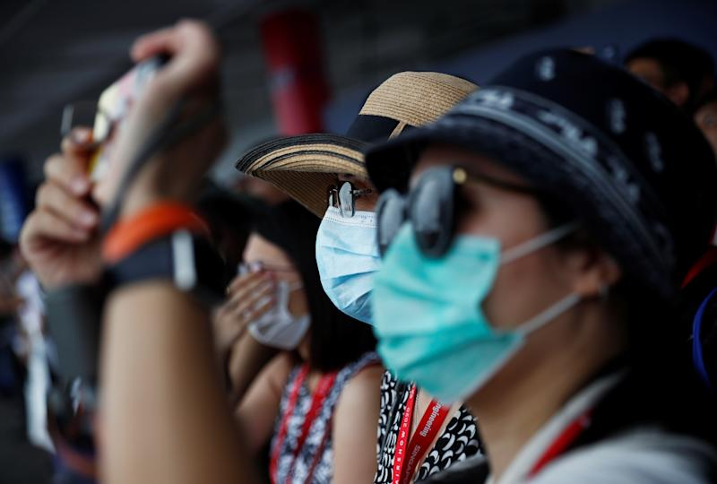 Spectators wearing masks in precaution of the coronavirus outbreak watch an aerial display at the Singapore Airshow on 11 February, 2020. (PHOTO: Reuters)
