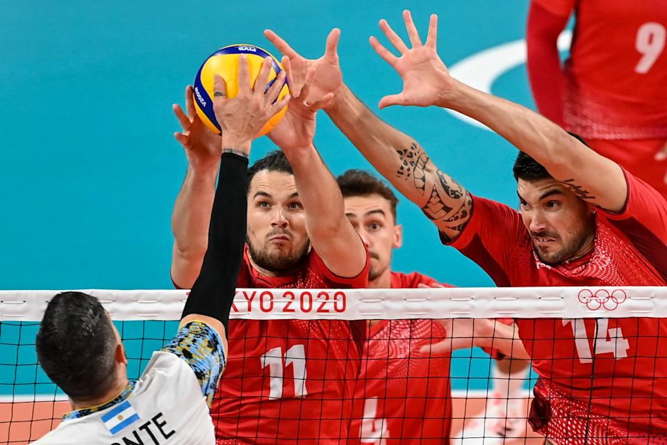 <p>France's Antoine Brizard (C) and France's Nicolas le Goff (R) block a shot in the men's preliminary round pool B volleyball match between Argentina and France during the Tokyo 2020 Olympic Games at Ariake Arena in Tokyo on July 28, 2021. (Photo by ANDREJ ISAKOVIC / AFP)</p>