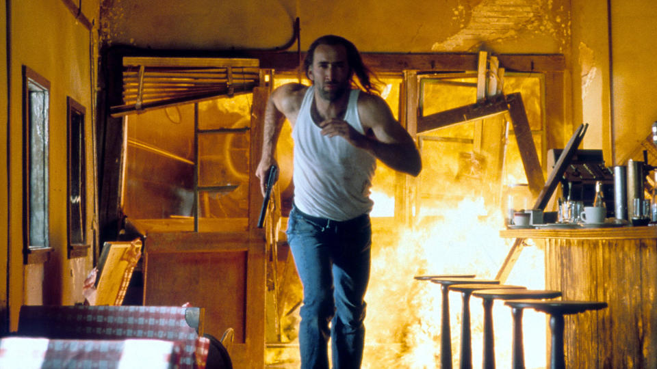 Nicolas Cage running through a burning building in a scene from the film 'Con Air', 1997. (Photo by Touchstone Pictures/Getty Images)