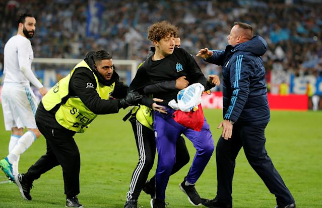 Soccer Football - Europa League Quarter Final Second Leg - Olympique de Marseille v RB Leipzig - Orange Velodrome, Marseille, France - April 12, 2018 Stewards tackle a pitch invader at the end of the match REUTERS/Jean-Paul Pelissier