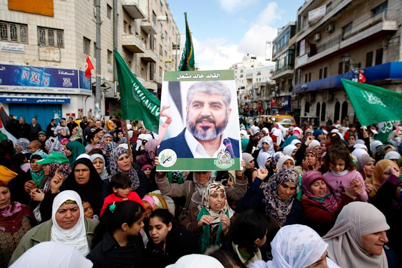 In this Dec 14, 2012 file photo, Palestinian supporters of Hamas hold a picture of leader Khaled Mashaal, during a rally to celebrate the 25th anniversary of the militant group, in the West Bank city of Ramallah - Credit: AP