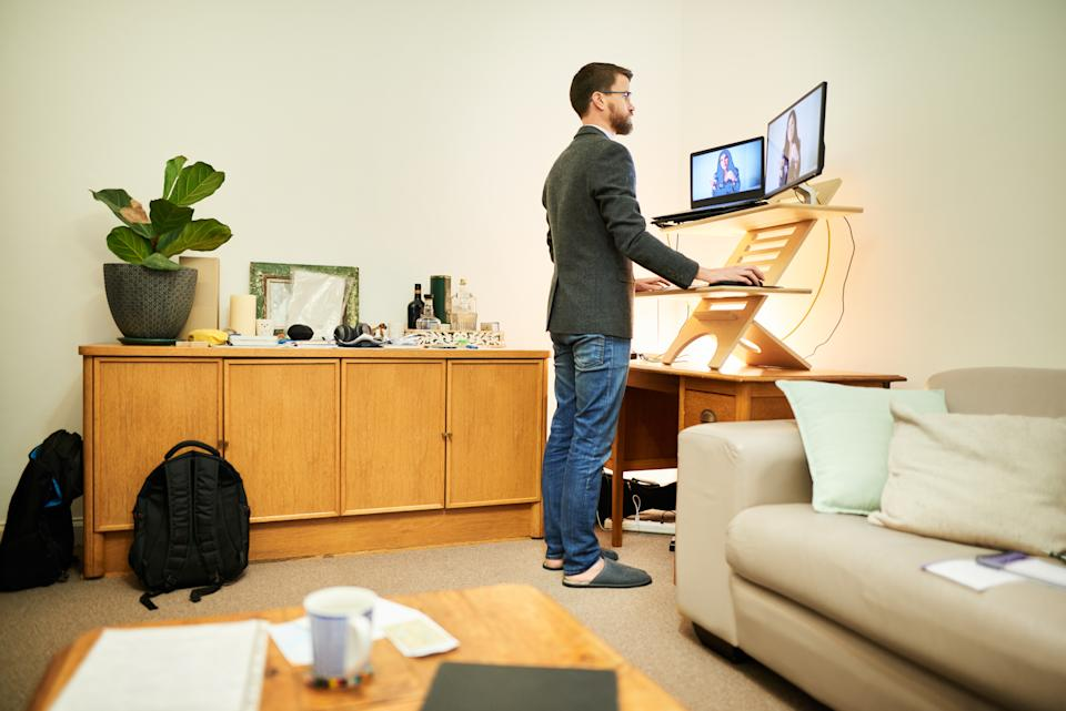 Young man having a online video meeting with office colleagues at a standing desk while working remotely from home