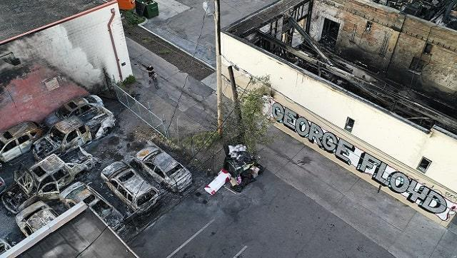 In this June 2, 2020, file photo, a cyclist stops besides a burned building and vehicles destroyed in a protest two days prior on East Lake Street in Minneapolis.