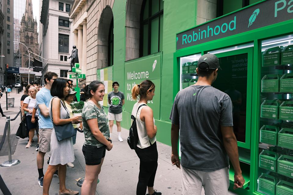 People wait in line for T-shirts at a pop-up kiosk for the online brokerage Robinhood along Wall Street after the company went public with an IPO  (Getty Images)