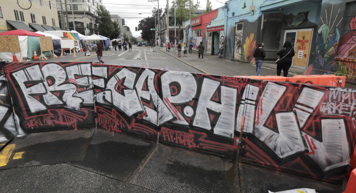 """A sign at an entrance to what has been named the Capitol Hill Occupied Protest zone in Seattle reads """"Free Cap Hill,"""" Monday, June 15, 2020. Protesters have taken over several blocks near downtown Seattle after officers withdrew from a police station in the area following violent confrontations. (AP Photo/Ted S. Warren)"""