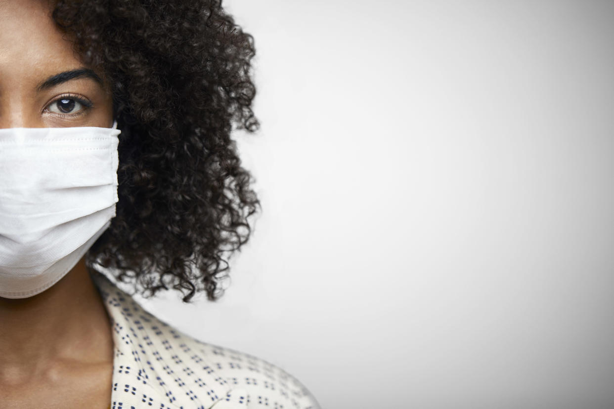 Closeup portrait of a young African American woman with face mask on the studio against white background.